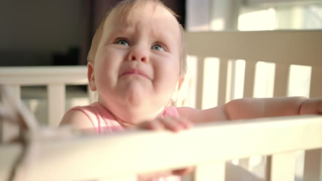 Sad baby crying in cot at home. Unhappy toddler standing in crib video