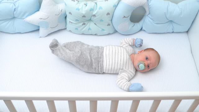 vídeos de stock, filmes e b-roll de bebê triste cospe chupeta e chora deitado em seu berço de visão de topo de alta vista câmera lenta - bico