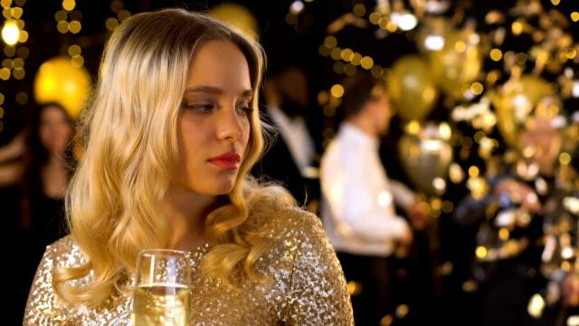 triste donna bionda che si sente sola alla festa, ballando le persone sullo sfondo, offesa - rivalità video stock e b–roll