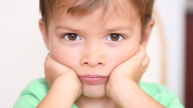 Sad bored little child boy close up