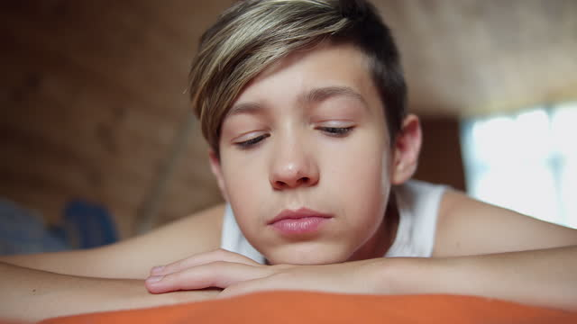 sad boy lies on the bed and thinks about something, sunny weather outside the window video