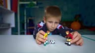 istock Sad boy playing figures of football players. The boy dreams of playing soccer with friends. 1228338260