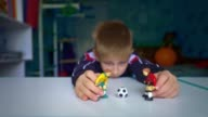 istock Sad boy playing figures of football players. The boy dreams of playing soccer with friends. 1264429847