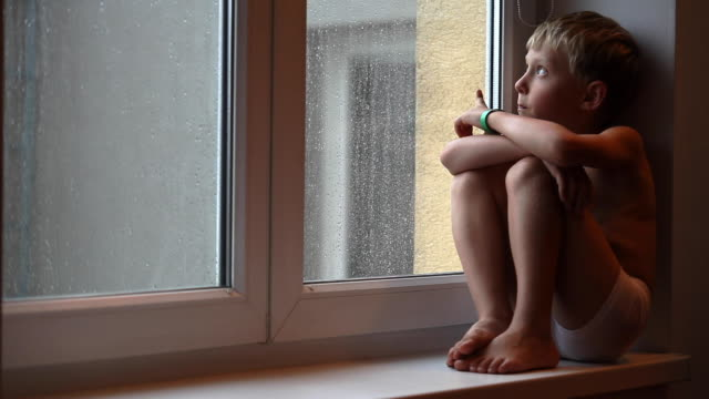 Sad boy siting on the windowsill on a rainy Global Coronavirus COVID-19 Outbreak day. World 2019–20 coronavirus pandemic and Stay at Home concept footage. Sad boy siting on the windowsill on a rainy Global Coronavirus COVID-19 Outbreak day. World 2019–20 coronavirus pandemic and Stay at Home concept footage. stay home stock videos & royalty-free footage