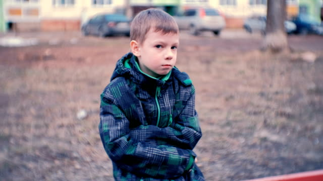 sad boy sitting on a bench. boy is lost and waiting for parents. - child abuse stock videos & royalty-free footage