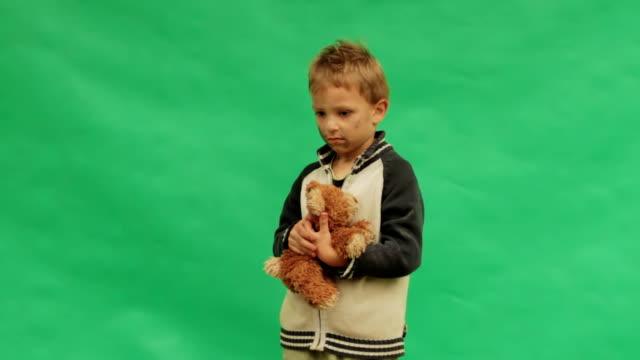 Sad boy stroking her teddy bear. Lonely. video