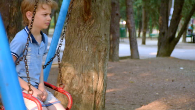 sad boy swinging on a swing in park video