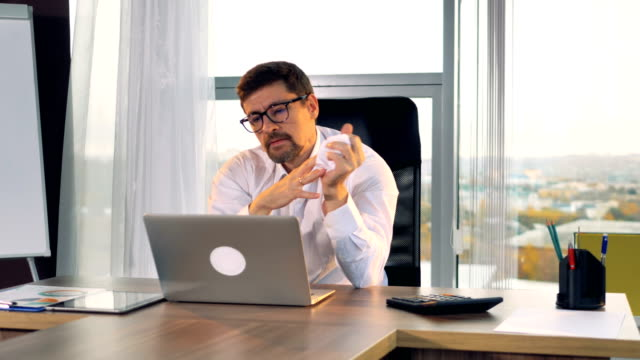 vídeos de stock e filmes b-roll de a sad businessman stares at his laptop screen. - amarrotado