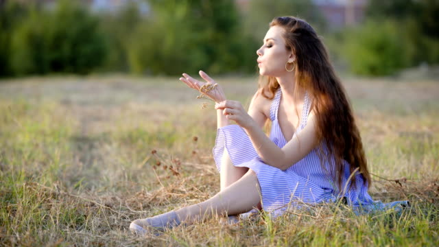 Sad, but very beauftiful woman is peacefully sitting in the field holding some wildflowers and giving some thoughts to life video