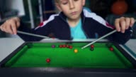 istock Sad child plays billiards with himself. Kid wants to make friends. Boy dreams of playing snooker with friends. 1229338200
