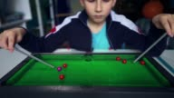 istock Sad child plays billiards with himself. Kid wants to make friends. Boy dreams of playing snooker with friends. 1264427306