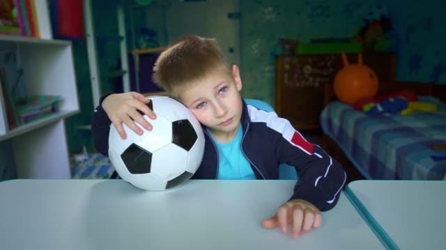悲しい子供はテーブルにサッカーボールを持って座っています。動揺した子供は検疫中に窓の外を見ます。 - サッカークラブ点の映像素材/bロール