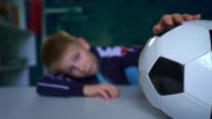 istock Sad child sits with a soccer ball at the table. An upset child looks out the window during quarantine. 1255049305