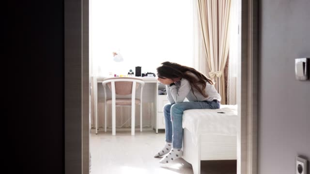 Sad child sitting on bed close her face with hands