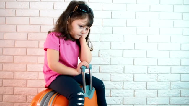Sad child. Sad child. A sad little girl is sitting on a travel suitcase. charming stock videos & royalty-free footage