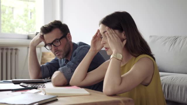 stockvideo's en b-roll-footage met triest paar tellen rekeningen, schuld-financiële problemen concept - overstuur