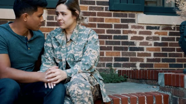 Sad couple prepare for the wife's military deployment A serious couple sit outside their home while dreading the wife's military deployment. They sit together on the porch holding hands. porch stock videos & royalty-free footage