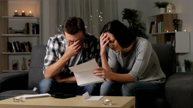 sad couple reading a letter in the night at home - debt stock videos & royalty-free footage