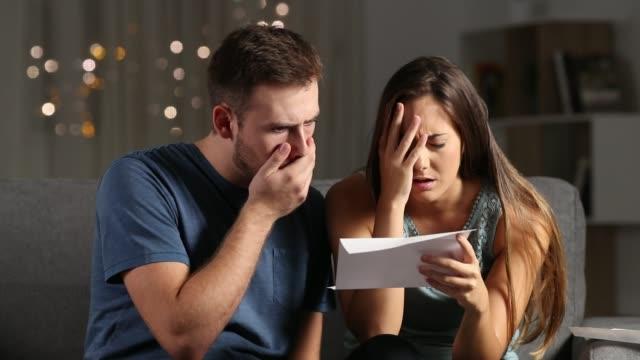 Couple triste lecture des mauvaises nouvelles, dans une lettre adressée dans la nuit - Vidéo