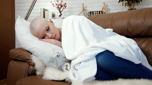 üzgün, depresif kanser hasta kadın kanepe ve acılarını yalan - meme hayvan vücudu bölümleri stok videoları ve detay görüntü çekimi