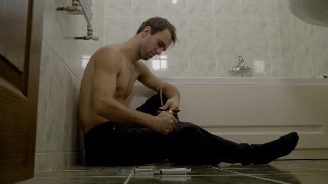 Sad depressed drug addicted young man sitting on the bathroom floor heating heroin and injecting it into his veins video