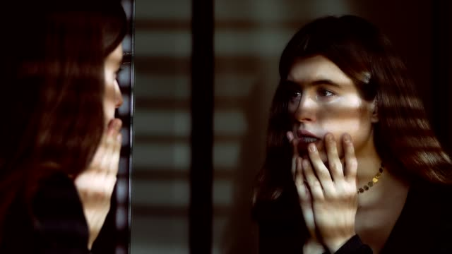 sad depressed woman looks herself in the mirror,touching her face in the dark - woman mirror video stock e b–roll