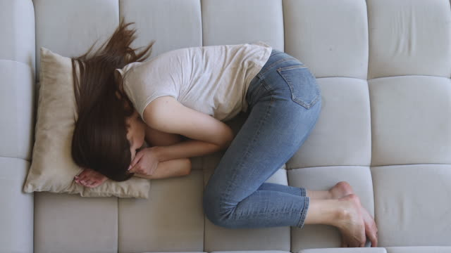 vídeos de stock, filmes e b-roll de mulher deprimida triste que encontra-se sozinho no sofá na posição fetal - posição