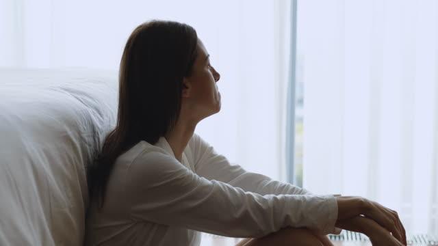 triste giovane donna depressa sedersi da sola sul pavimento in camera da letto - fragilità video stock e b–roll