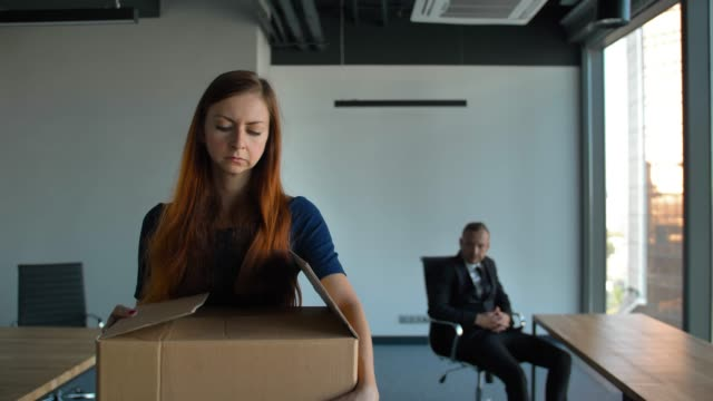Sad employee packing her belongings and leaving the office after being fired