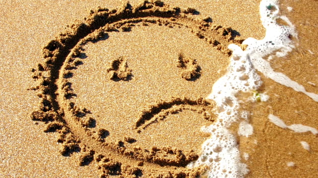 Sad face drawn in sand, washed away by sea. A sad face is drawn in the sand on a beach. Waves roll in and wash the drawing away. relationship breakup stock videos & royalty-free footage