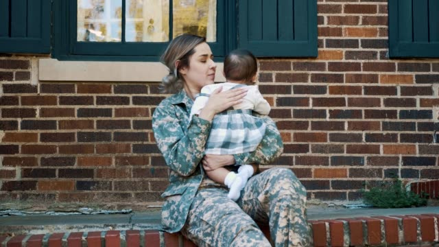 Sad female soldier dreads leaving baby girl for military assignment As she sits on the front porch of her home, a sad female soldier holds her baby girl before leaving for military assignment. She rocks her sleepy baby and gives her sweet kisses. camouflage clothing stock videos & royalty-free footage