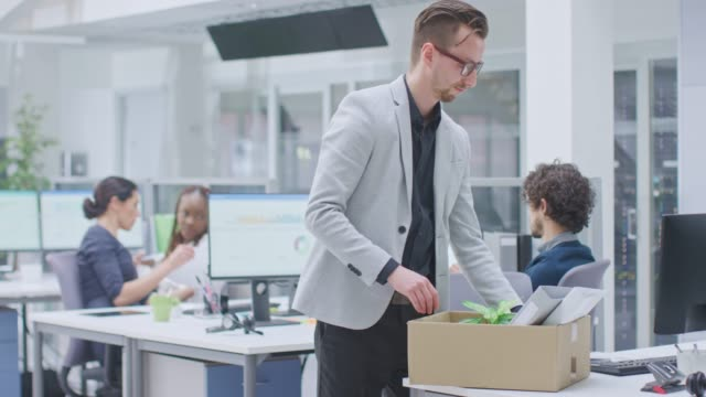 sad fired / let go office worker packs his belongings into cardboard box and leaves office. workforce reduction, downsizing, reorganization, restructuring, outsourcing. mass unemployment market crisis - потеря стоковые видео и кадры b-roll
