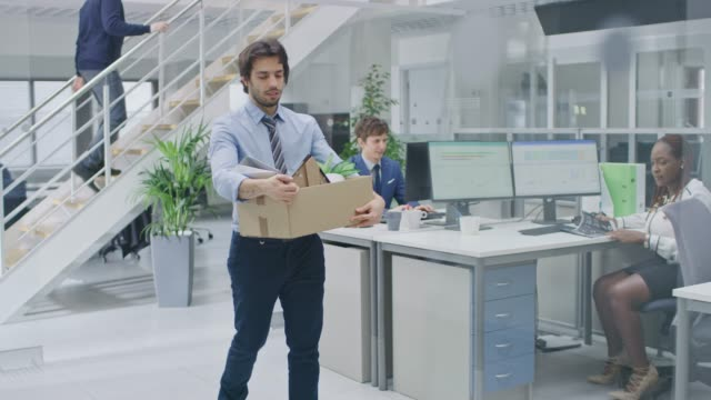 vídeos de stock e filmes b-roll de sad fired / let go office worker packs his belongings into cardboard box and leaves office. workforce reduction, downsizing, reorganization, restructuring, outsourcing. mass unemployment market crisis - ser despedido