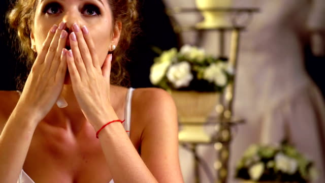 Sad girl in wedding dress looking pictures. FullHD video