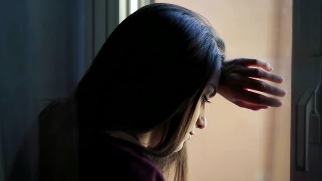 vídeos de stock, filmes e b-roll de menina triste perto de janela pensar uma coisa: problemas com alguns pensamentos. - pena