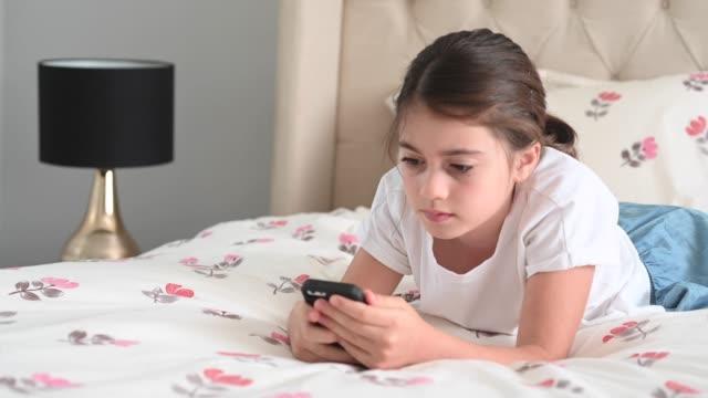 stockvideo's en b-roll-footage met droevig meisje dat een het intimideren bericht op sociale media leest - kids online abuse