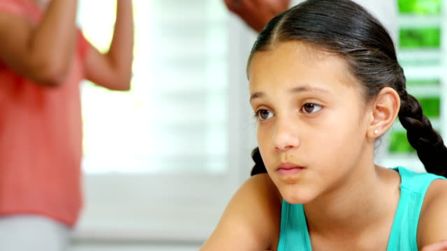 Sad girl sitting at table while parents arguing in background video