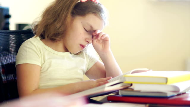 Sad girl sitting at the table with a pile of books. She rubs her eyes and wants to sleep. Problems of school education. Back to school Sad girl sitting at the table with a pile of books. She rubs her eyes and wants to sleep. Problems of school education. Back to school. educational exam stock videos & royalty-free footage