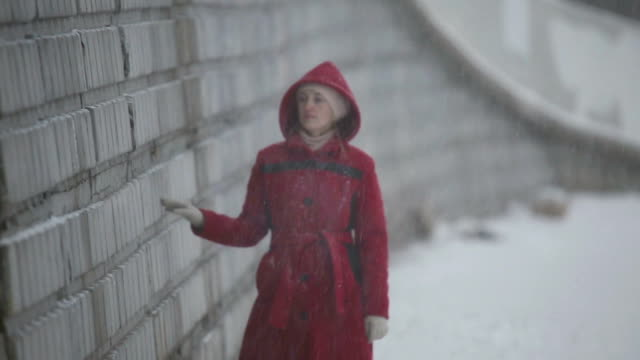 Sad girl walking on the river promenade in winter Sad girl in the red coat walking on the river promenade in winter, she was upset and clung to the wall depression land feature stock videos & royalty-free footage
