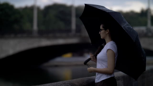 sad girl with an umbrella stands near a small river in the background of the bridge, thinks about something, the end of the rain - mockup outdoor rain video stock e b–roll