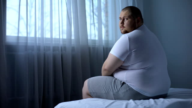 Sad heavy man sitting on bed at home, health problem, depression, insecurities Sad heavy man sitting on bed at home, health problem, depression, insecurities large build stock videos & royalty-free footage