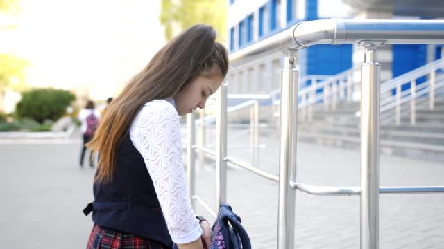 vídeos y material grabado en eventos de stock de triste chica de secundaria regresa a casa de la escuela. colegiala adolescente lanza la mochila en su hombro y camina a casa después de la escuela. - regreso a clases