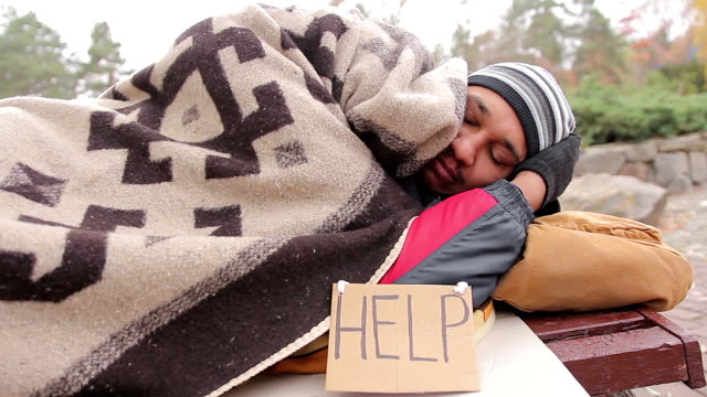 Sad homeless man suffering from cold, sleeping on bench covered with blanket video