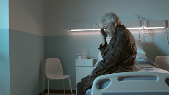 vídeos y material grabado en eventos de stock de triste anciano desesperado sentado en una cama de hospital solo - geriatría