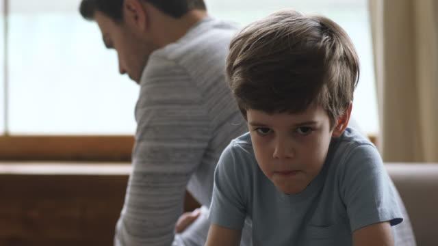 ledsen unge son tänker på konflikter vända tillbaka till pappa - parent talking to child bildbanksvideor och videomaterial från bakom kulisserna