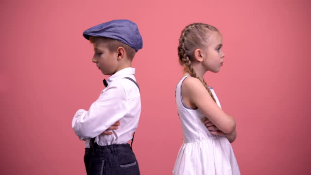 Sad kids couple standing back in silence after quarrel, isolated pink background Sad kids couple standing back in silence after quarrel, isolated pink background back to back stock videos & royalty-free footage