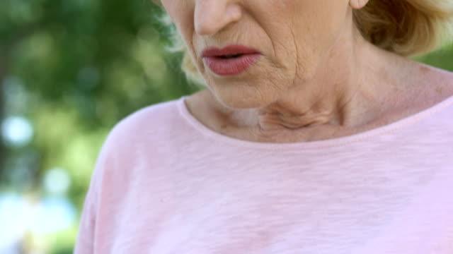 vídeos de stock e filmes b-roll de sad lady holds hands on chest, progressive breast cancer, bad diagnosis, pain - enfarte