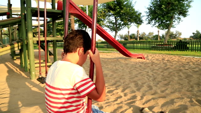 Sad little boy at the playground video
