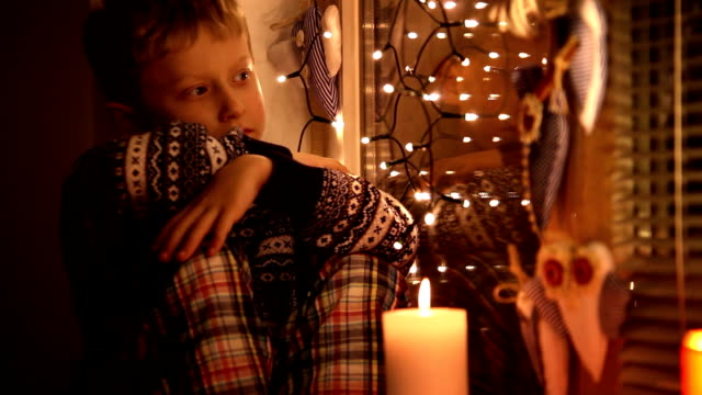 Sad little boy clad in his pajamas and winter-pattern sweater waiting for Santa video