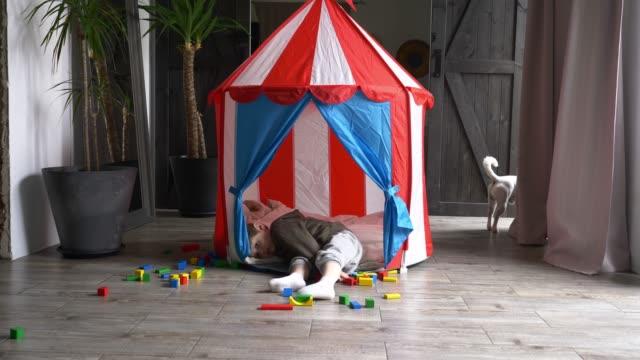 sad little boy in a small children's house - solo bambini maschi video stock e b–roll